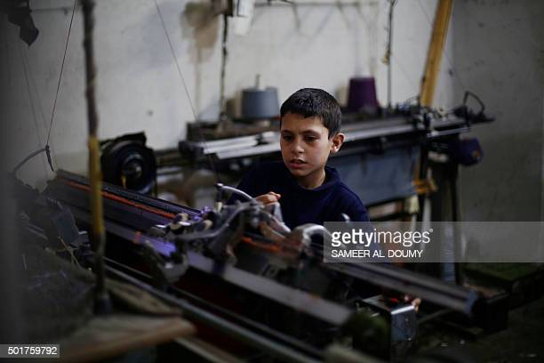 A boy helps his father at a clothing factory in the eastern Ghouta region a rebel stronghold east of the Syrian capital Damascus on December 17 2015...