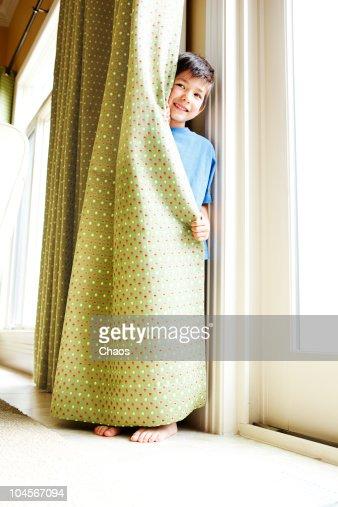 Boy hides behind a Curtain
