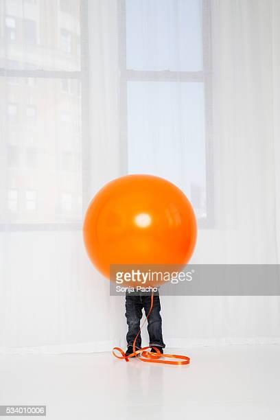 Boy Hiding Behind Balloon