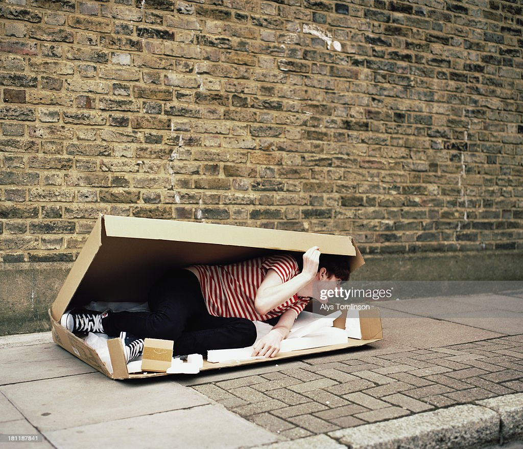 Boy hiding in a cardboard box outdoors : Stock Photo