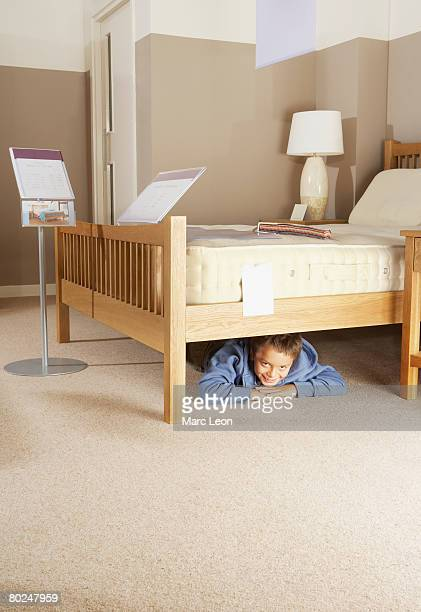 Boy hiding under bed in furniture store.