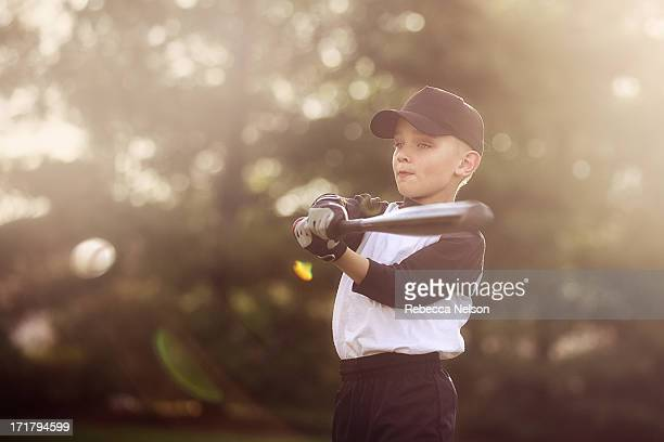 boy hitting baseball with bat