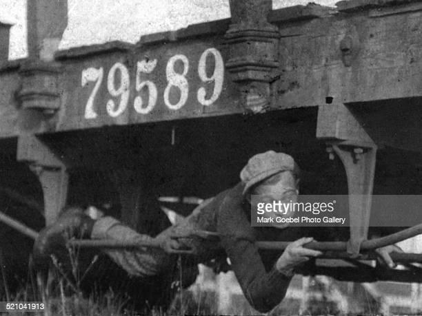 Boy hobo hanging on rail 1930s