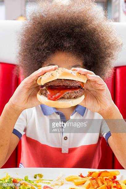 Boy (10-11) hold hamburger in front of his face