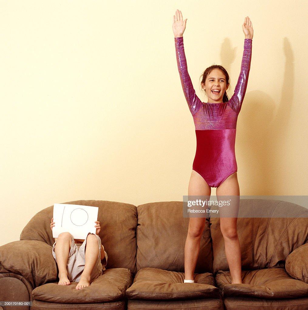 Boy (4-6) holding '10' sign beside girl (9-11) in leotard on sofa : Stock Photo