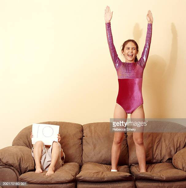 Boy (4-6) holding '10' sign beside girl (9-11) in leotard on sofa