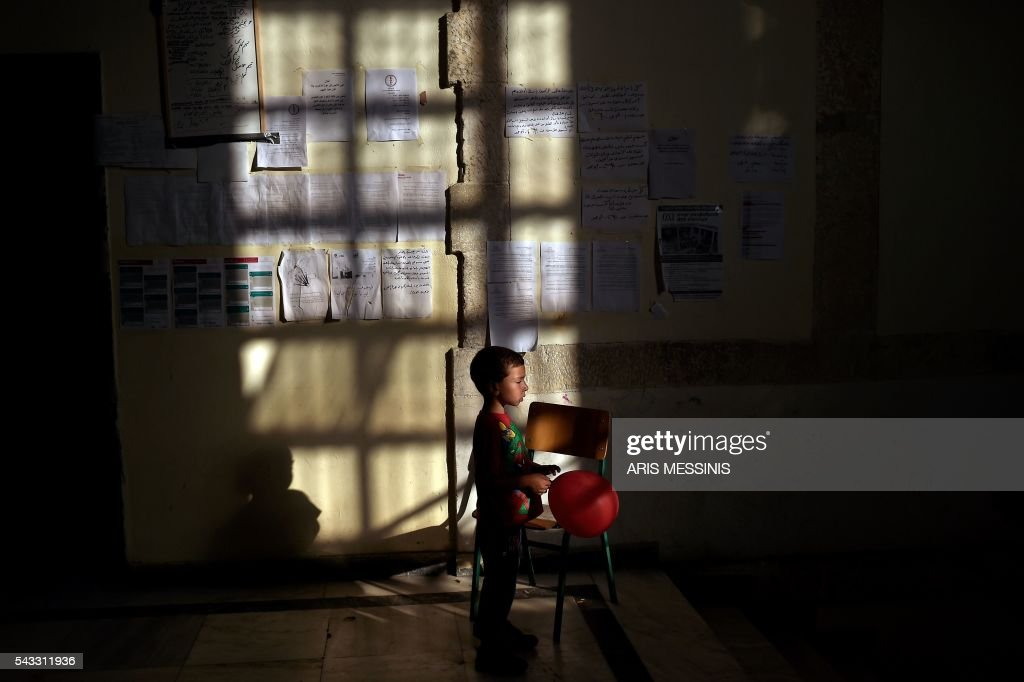 A boy holding a baloon stands in an abandoned school used by volunteers for hosting families of refugeees from Syria and Afghanistan in Athens on June 27, 2016. / AFP / ARIS