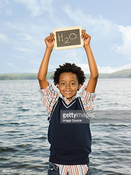 A boy holding a blackboard with the symbol for water