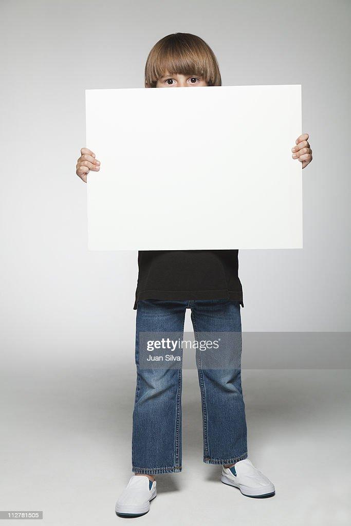 Boy holding a blank whiteboard, portrait : Stock Photo