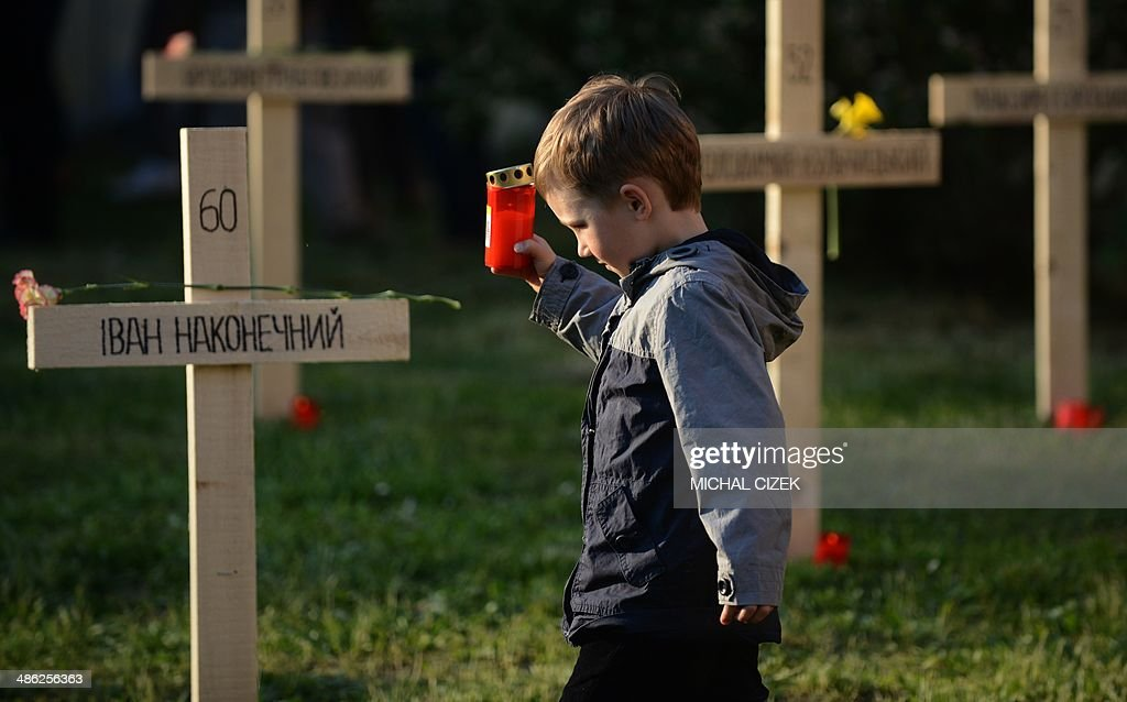 A boy holding a candle walks past the crosses in a mock graveyard commemorating the people that died during recent protests in Ukraine on April 23, 2014, in Prague.