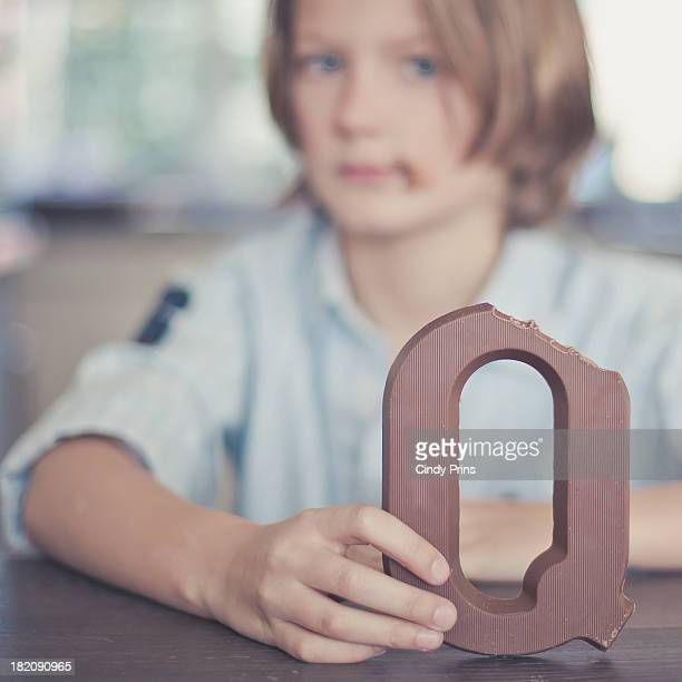 Boy holding a chocolate letter
