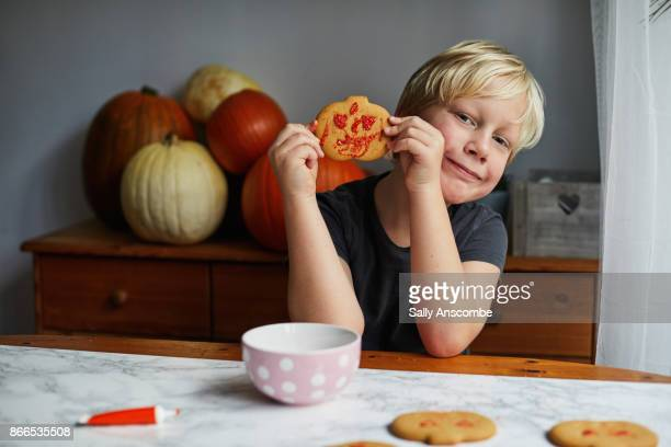 Boy holding a decorated pumpkin biscuit
