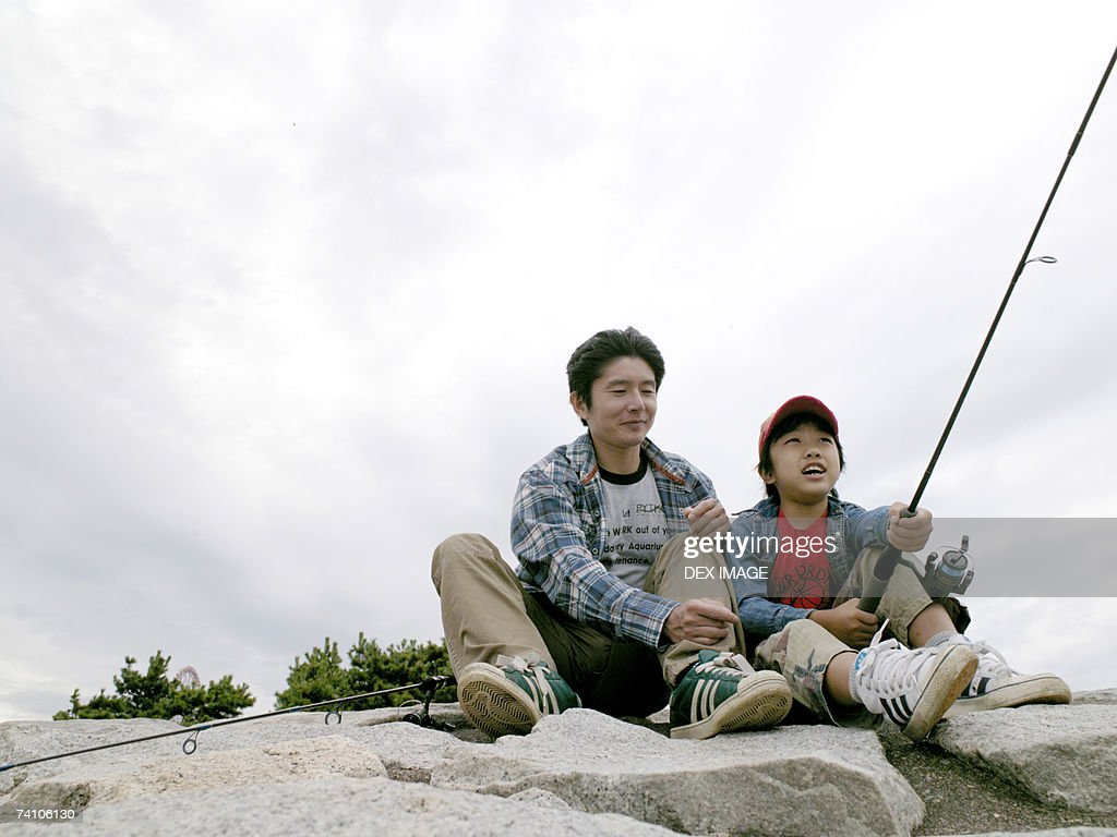 Boy holding a fishing rod with his father beside him : Stock Photo