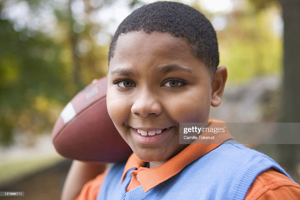 Boy holding a football smiling : Stock Photo