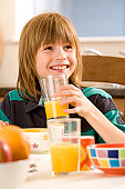 Boy holding a glass of orange juice and smiling