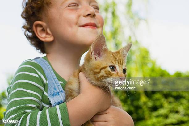A boy holding a kitten
