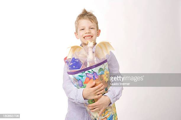 Boy holding a large cornet of cardboard filled with sweets and little presents given to children in Germany on their first day at school