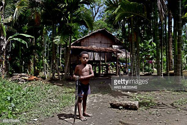 A boy holding a machete stands outside his house in the village of Tora in the jungle of Papua New Guinea on September 8 2014 AFP PHOTO / ARIS...