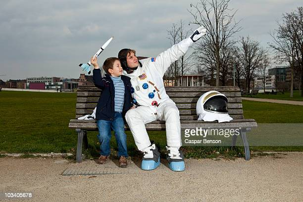 A boy holding a model rocket sitting with an astronaut on a park bench