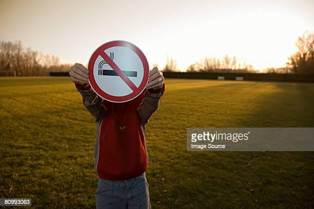 Boy holding a no smoking sign