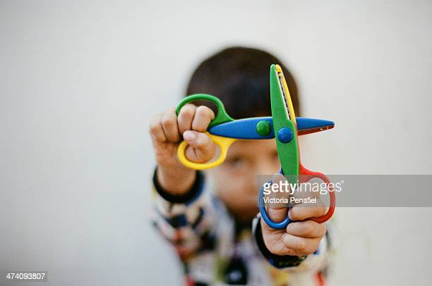 Boy holding a pair of colourful scissors