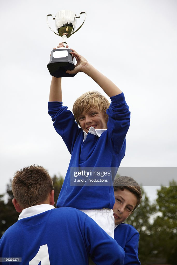 Boy holding a trophy in the air : Foto de stock