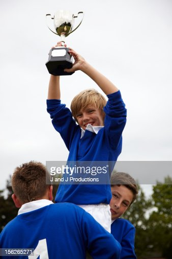 Boy holding a trophy in the air : Bildbanksbilder