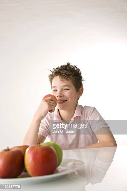 A boy holding an apple in his hand, smiling