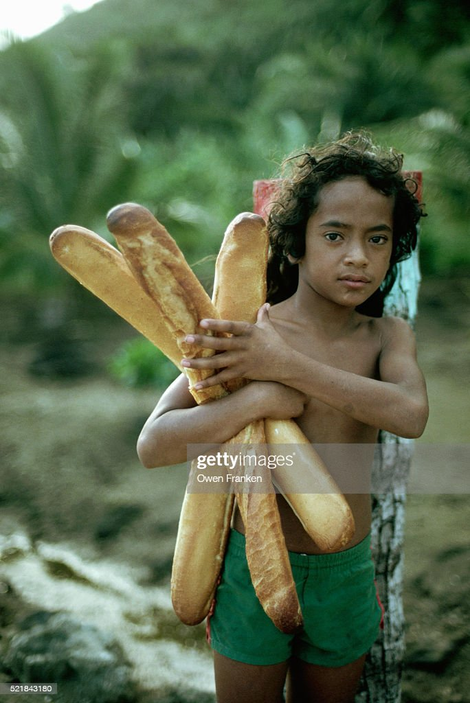 Boy Holding Armful of Baguettes