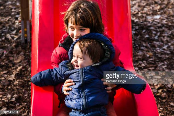 Boy holding baby brother on playground slide