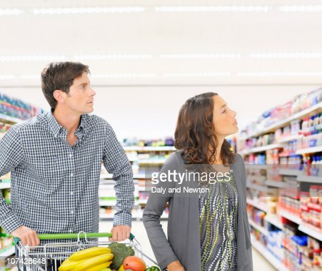 Boy holding bag full of fruits and vegetables in grocery store : Foto de stock
