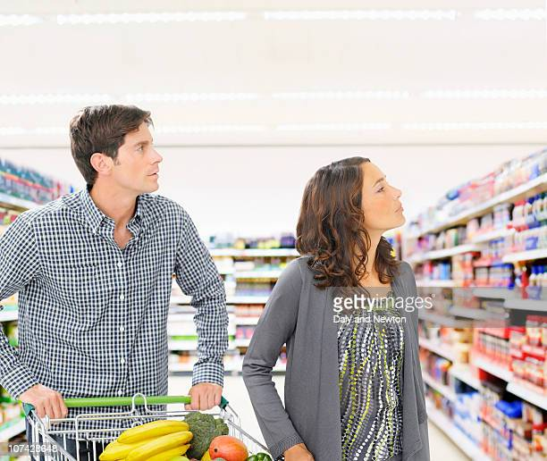Boy holding bag full of fruits and vegetables in grocery store