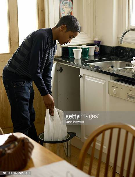 Boy (12-13) holding bag of waste in kitchen