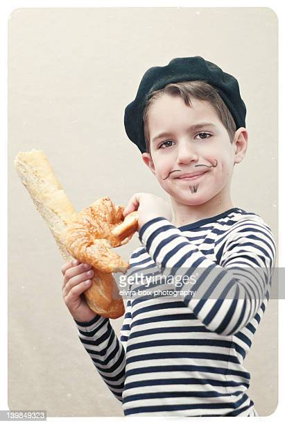Boy holding baguette and croissant