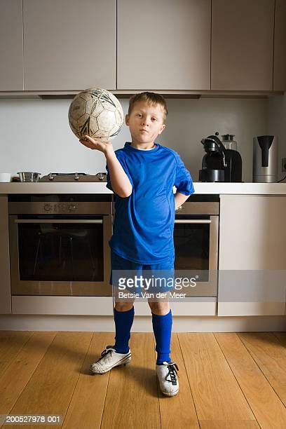 Boy (8-10) holding ball in blue football strip in kitchen, portrait