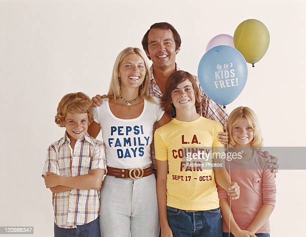 Boy holding balloons standing with family against white background, smiling, portrait