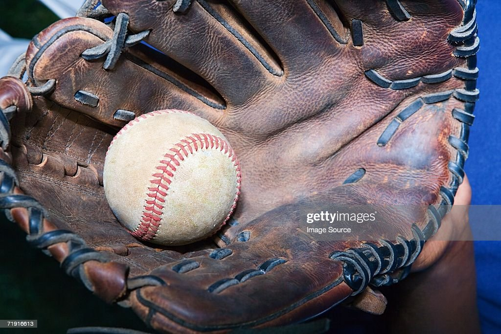 Boy holding baseball in a baseball glove