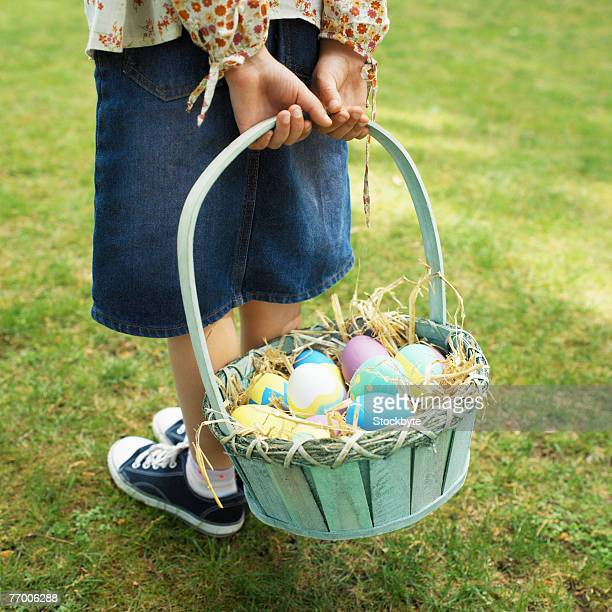 Boy (10-11) holding basket of eggs on lawn, low section