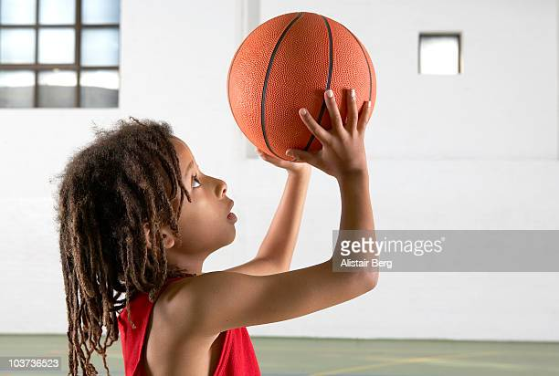 Boy holding basketball in gymnasium
