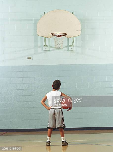 Boy (8-10) holding basketball, looking at hoop, rear view