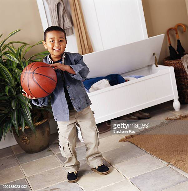 Boy (5-7) holding basketball, portrait