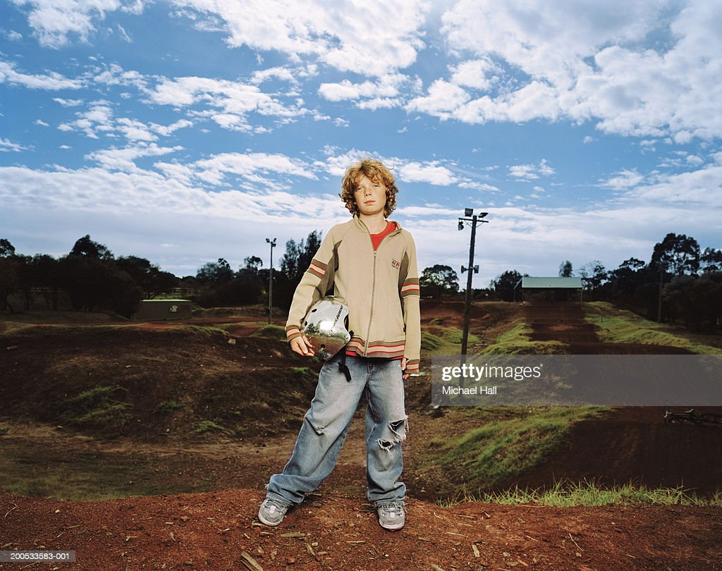 Boy (9-11) holding bicycle helmet, standing by bike track, portrait : Stock Photo