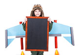 Closeup portrait of child with crafted jet pack wings holding blank blackboard with space for text, Isolated on white background, Children imagination and motivation concept