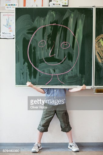 Boy holding blackboard with smiley face drawing : Stock-Foto