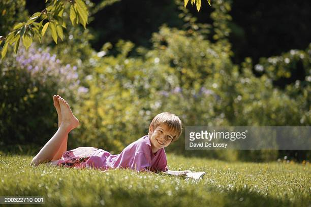 Boy (6-9) holding book, lying on garden, ground view