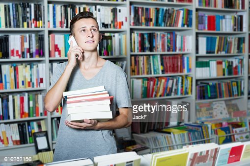 Boy holding books and talking on mobile phone in shop : Foto de stock