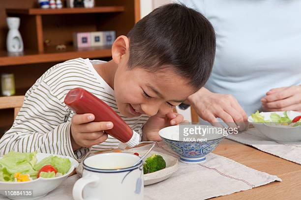 Boy Holding Bottle of Ketchup