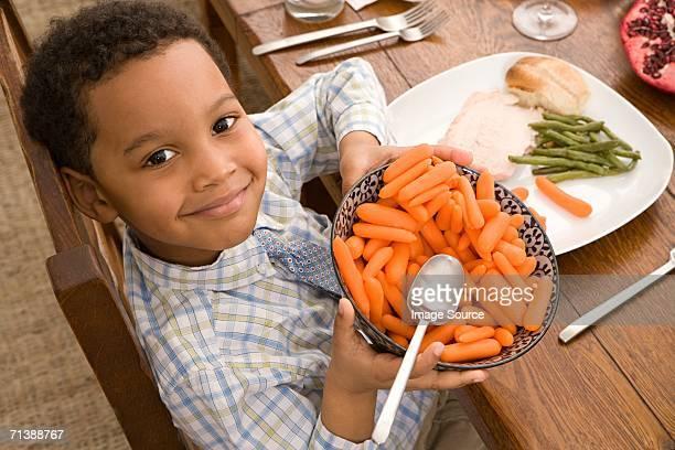 Garçon tenant un bol de carottes