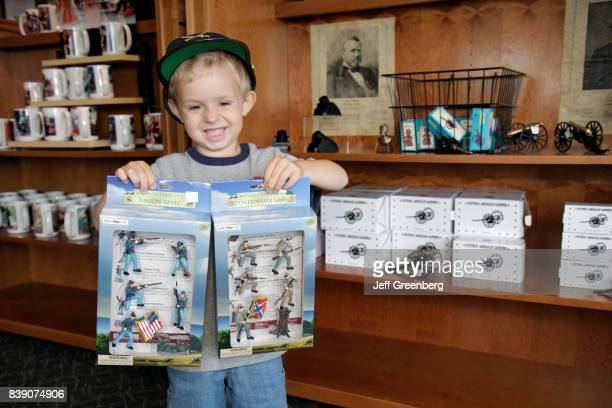 A boy holding boxes of toy soldiers in the gift shop at the Civil War Museum in Kenosha