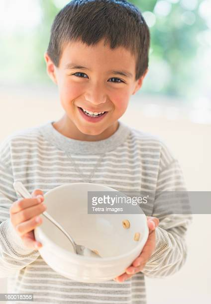 Boy (6-7) holding breakfast bowl